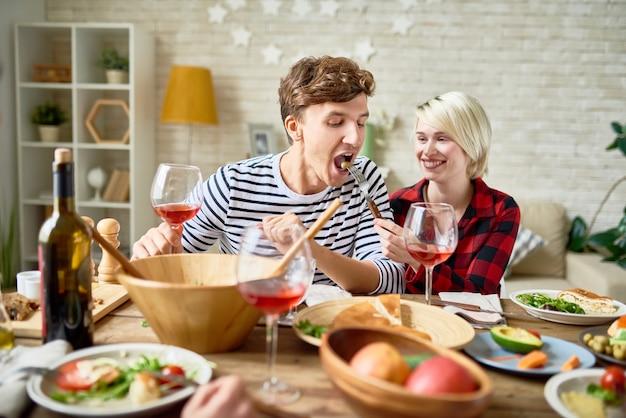 Glückliches junges paar am festlichen esstisch