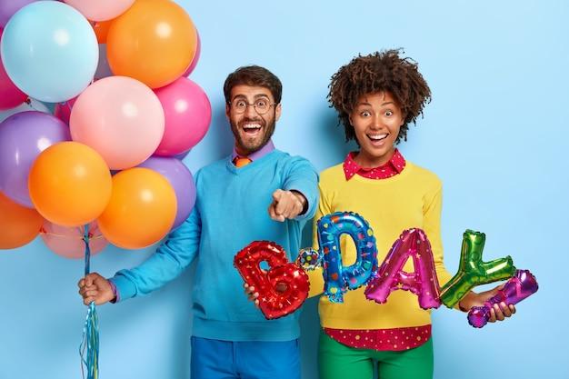 Glückliches junges paar auf einer party, die mit luftballons aufwirft