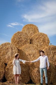 Glückliches junges paar auf stroh, romantisches menschenkonzept, schöne landschaft, sommersaison.