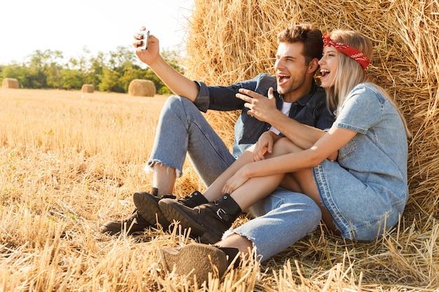 Glückliches junges paar, das am weizenfeld sitzt