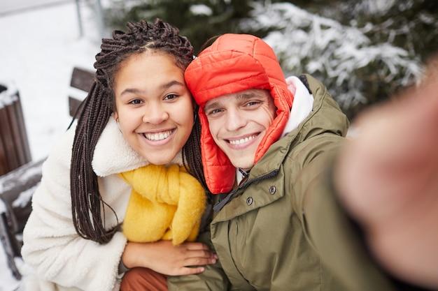 Glückliches junges paar, das an der kamera des mobiltelefons im wintertag draußen lächelt