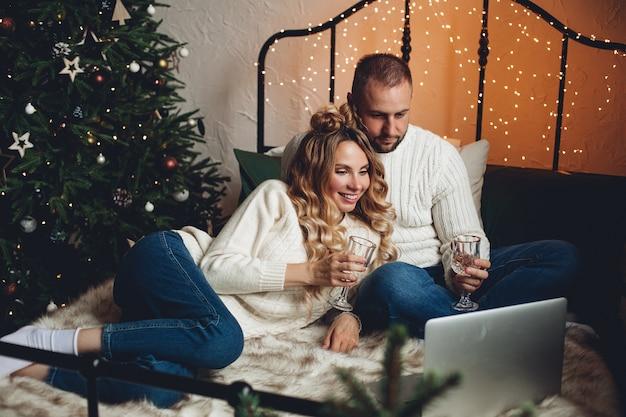 Glückliches junges paar, das auf bett sitzt, während brille hält und videoanruf auf laptop macht