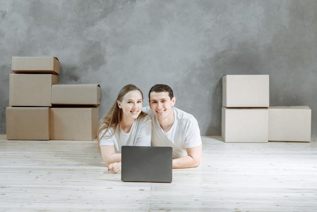 Glückliches junges paar, das auf dem boden nahe den umzugskartons in der wohnung liegt. t.