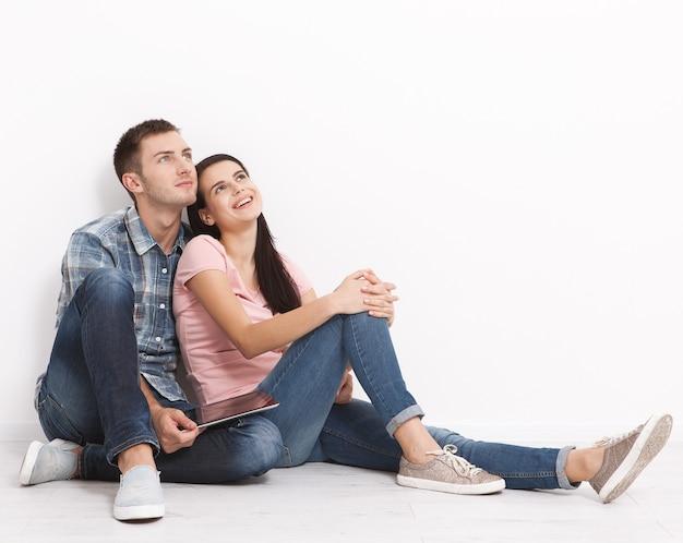 Glückliches junges paar, das auf dem boden sitzt und nach oben schaut, während es sein neues zuhause und einrichtung träumt