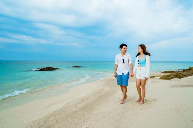 Glückliches junges paar, das auf dem meeresstrand bei koh munnork island, rayong, thailand geht