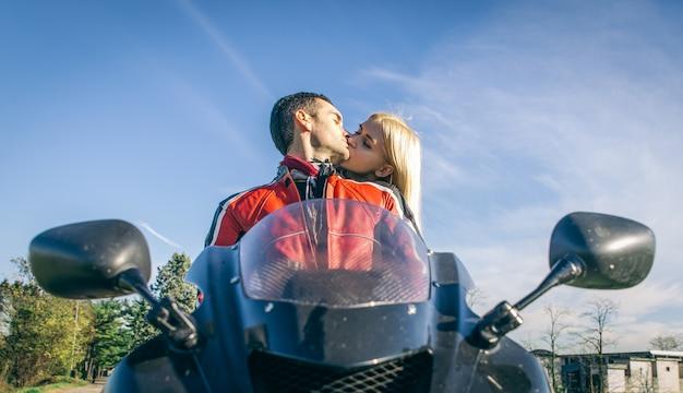 Glückliches junges paar, das auf dem motorrad küsst