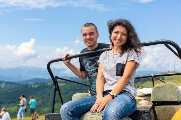 Glückliches junges paar, das auf dem schmutzigen geländewagen ausruht
