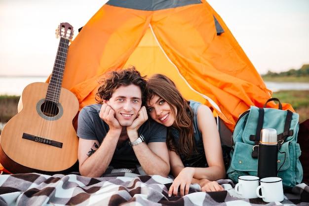 Glückliches junges paar, das auf dem strand kampiert, der im zelt liegt