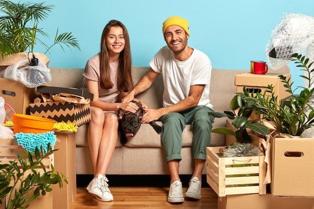 Glückliches junges paar, das auf der couch sitzt, umgeben von kisten