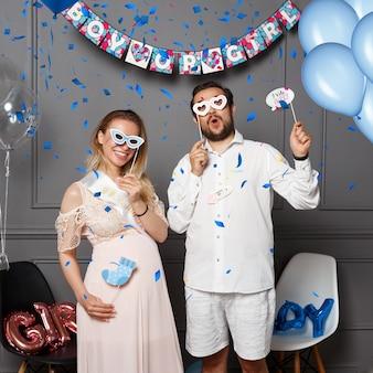 Glückliches junges paar, das ballons mit aufschrift junge oder mädchen während des geschlechts hält, enthüllt party im inneren, über farbigem konfetti und luftballons.
