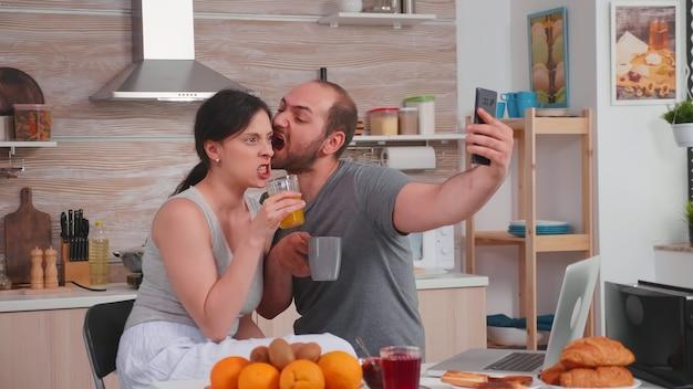 Glückliches junges paar, das beim frühstück selfies macht. fröhlicher verheirateter ehemann und ehefrau machen lustige gesichter beim fotografieren während des frühstücks in der küche.