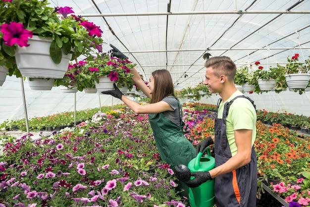 Glückliches junges paar, das blumen mit einer gießkanne im blumengartenzentrum gießt