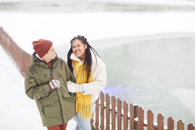 Glückliches junges paar, das die frische luft genießt, die im winterpark geht