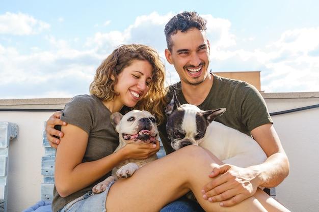 Glückliches junges paar, das draußen mit hund spielt. horizontale ansicht des paares, das mit bulldogge auf couch lacht.