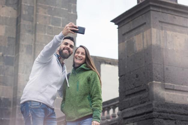 Glückliches junges paar, das ein selfie mit handy am kalten wintertag in der altstadt las palmas, spanien nimmt.