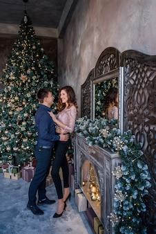 Glückliches junges paar, das elegante kleidung im raum mit weihnachtslichtern verziert trägt