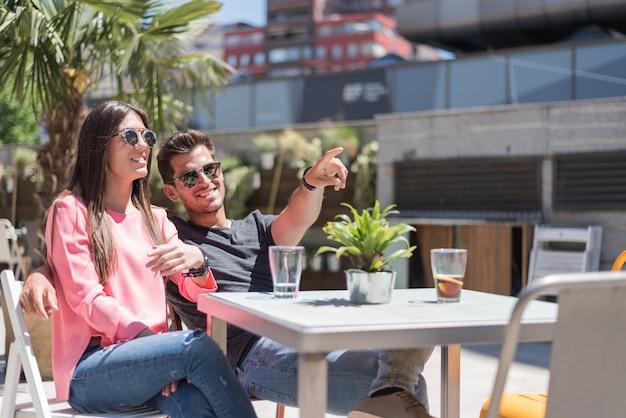 Glückliches junges paar, das entspannt auf einer restaurantterrasse sitzt