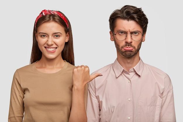 Glückliches junges paar, das gegen die weiße wand aufwirft