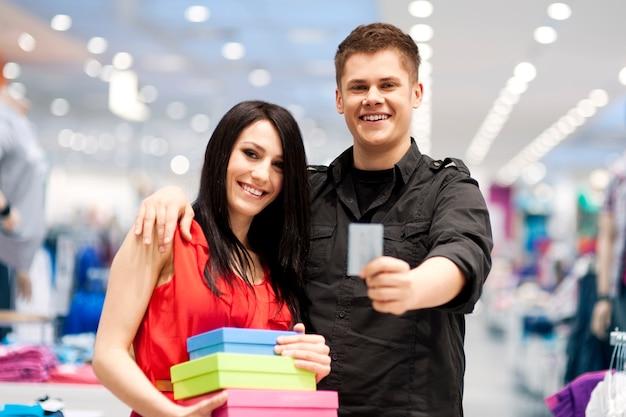 Glückliches junges paar, das geld am bekleidungsgeschäft ausgibt