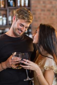 Glückliches junges paar, das getränkegläser hält