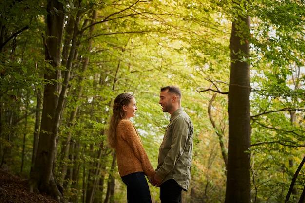 Glückliches junges paar, das hände hält und einander ansieht