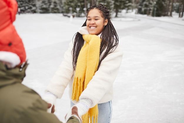 Glückliches junges paar, das hände zusammen im freien im winterwald geht
