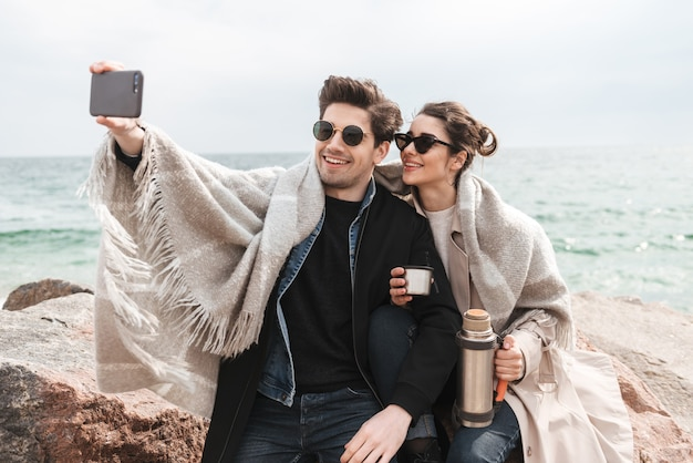 Glückliches junges paar, das herbstmäntel trägt, verbringt zeit zusammen am meer, sitzt in einer decke bedeckt, trinkt kaffee aus der thermoskanne, macht ein selfie