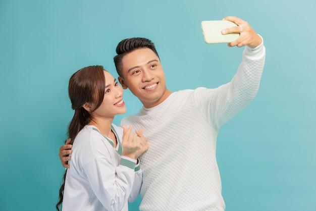 Glückliches junges paar, das herz koreanischen stil zeigt, während ein selfie zusammen über blau isoliert nimmt