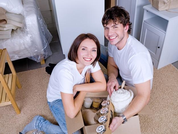 Glückliches junges paar, das ihre sachen nach dem umzug auspackt