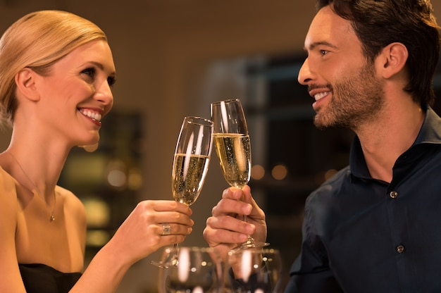 Glückliches junges paar, das ihren hochzeitstag in einem luxusrestaurant feiert.