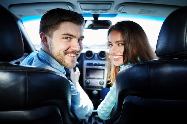 Glückliches junges paar, das im auto sitzt und kamera betrachtet und lächelt.