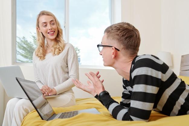 Glückliches junges paar, das im schlafzimmer mit laptops sitzt und die neuesten nachrichten bespricht