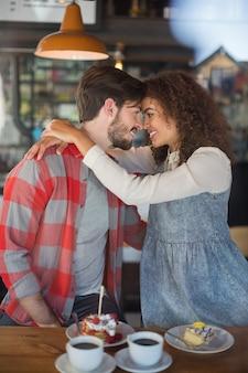 Glückliches junges paar, das in der kneipe umarmt