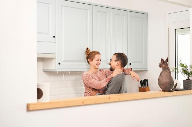Glückliches junges paar, das in der küche zu hause lacht