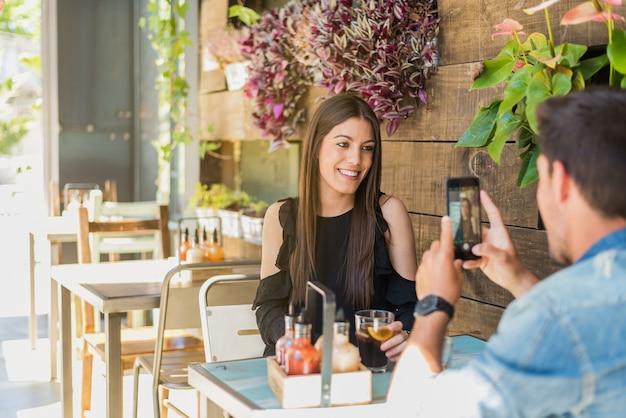 Glückliches junges paar, das in einem restaurant mit einem smartphone sitzt, das ein foto macht