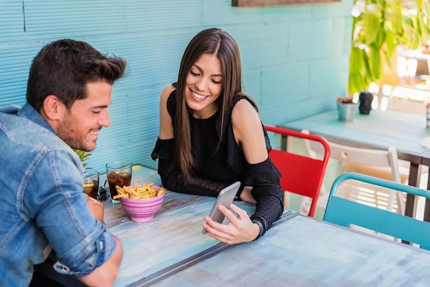 Glückliches junges paar, das in einem restaurant mit einem smartphone sitzt