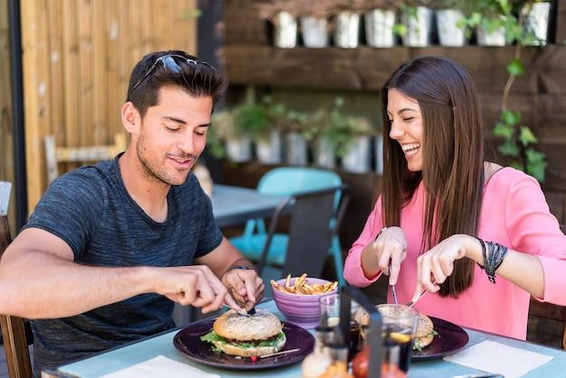Glückliches junges paar, das in einer restaurantterrasse sitzt, die einen burger isst