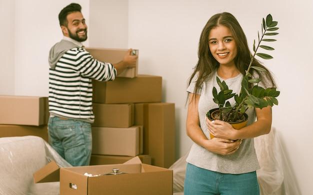 Glückliches junges paar, das in ihrem neuen zuhause umzieht