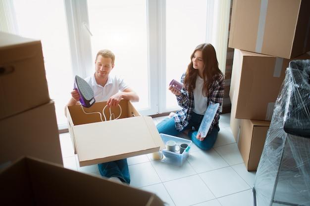 Glückliches junges paar, das kisten auspackt oder packt und in ein neues zuhause zieht.