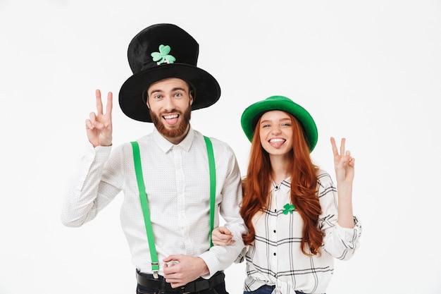 Glückliches junges paar, das kostüme trägt, stpatrick 's day isoliert über weißer wand feiert, spaß zusammen hat, friedensgeste