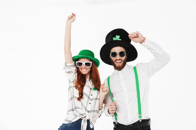 Glückliches junges paar, das kostüme trägt, stpatrick's day isoliert über weißer wand feiert, spaß zusammen hat, mit sonnenbrille posierend