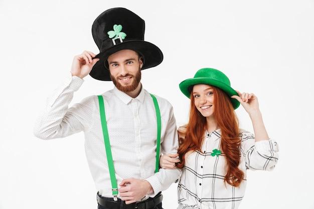 Glückliches junges paar, das kostüme trägt, stpatrick 's day isoliert über weißer wand feiert, spaß zusammen hat
