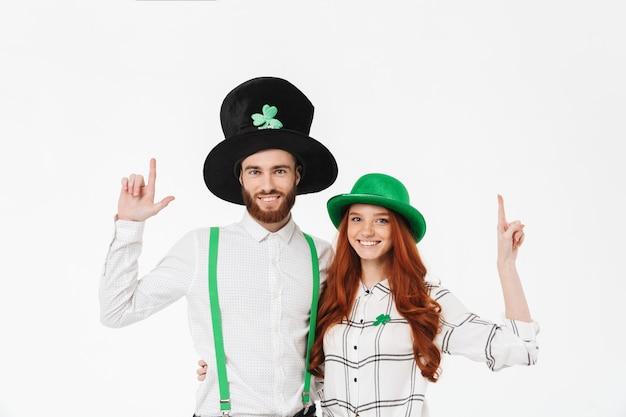 Glückliches junges paar, das kostüme trägt und stpatrick 's day isoliert über weißer wand feiert und finger zeigt