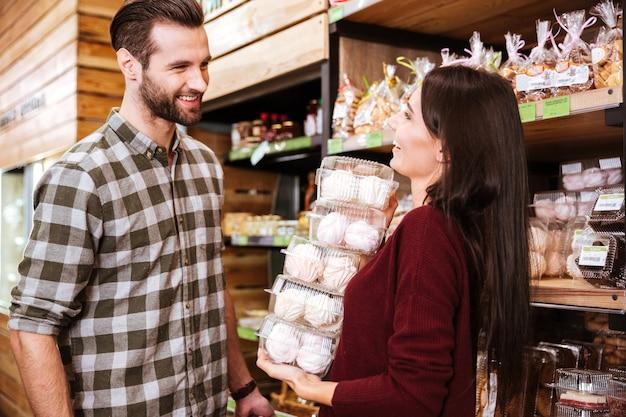 Glückliches junges paar, das marshmallows im lebensmittelgeschäft kauft?