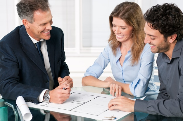 Glückliches junges paar, das mit einem immobilienmakler über ihre neuen hauspläne bespricht
