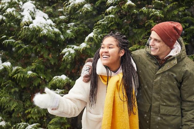 Glückliches junges paar, das nahe schneebedecktem baum steht und das winterwetter im wald genießt