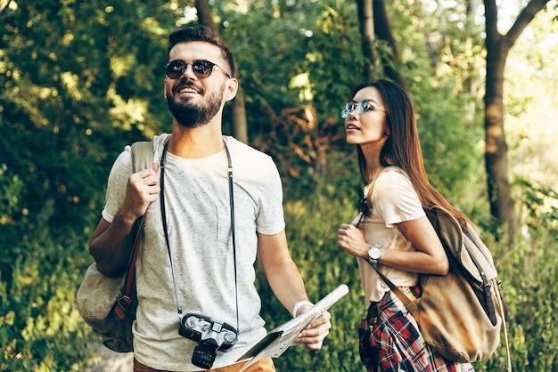 Glückliches junges paar, das neue orte erkundet und beim spaziergang im freien lächelt?
