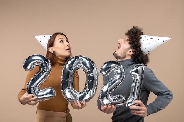 Glückliches junges paar, das oben schaut, trägt neujahrshut-posen für kamera-mädchen, das und und kerl mit und auf grau zeigt