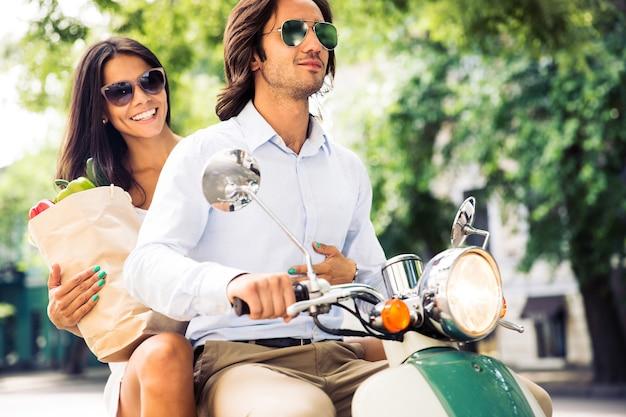 Glückliches junges paar, das roller fährt, während frau tasche voller lebensmittel hält. sommerzeit.