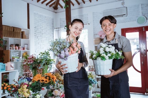 Glückliches junges paar, das schürze hält, die eimerblume lächelnd betrachtet kamera. arbeiten im blumenladen